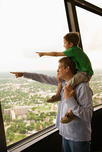 Stock Photo: 1525R-108936 Father and son pointing from observation deck at Tower of the Americas in San Antonio, Texas.