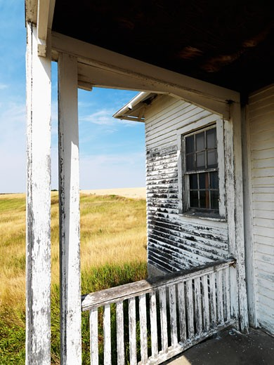 Stock Photo: 1525R-109254 View from porch of weathered abandoned building in grassland.
