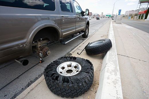 Stock Photo: 1525R-109430 Vehicle brokendown along roadside with damaged tire needing replacement.