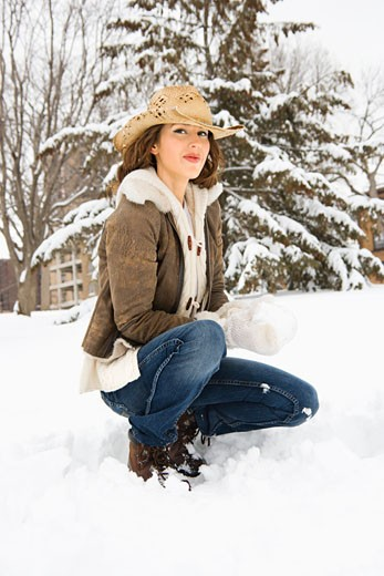 Stock Photo: 1525R-109715 Caucasian young adult female looking at viewer while kneeling in snow with snowball and wearing straw cowboy hat.