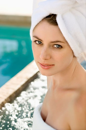 Caucasian mid-adult woman wearing white terry robe smiling at viewer next to pool. : Stock Photo