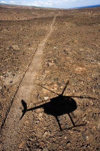Pathway leading through rocky terrain with shadow of helicopter flying overhead in Maui, Hawaii. : Stock Photo