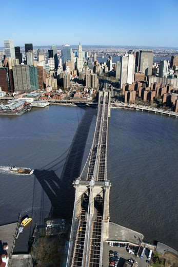 Stock Photo: 1525R-110007 Aerial view of Brooklyn Bridge with East River and Manhattan buildings in New York City.
