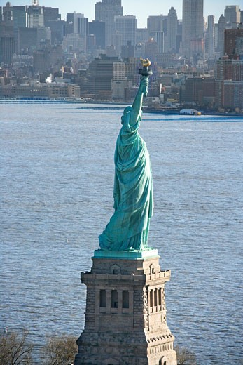 Aerial view of Statue of Liberty with Manhattan, New York buildings in background. : Stock Photo