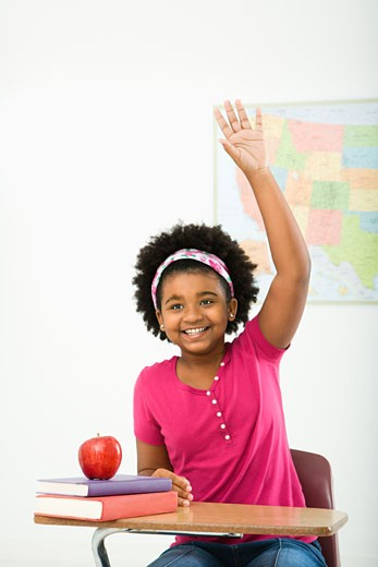 Stock Photo: 1525R-110154 African American girl sitting in school desk raising hand and smiling at viewer.