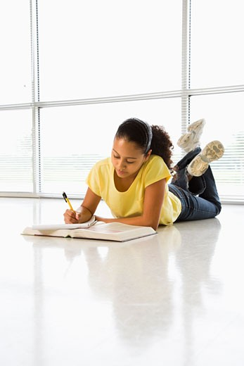African American girl lying on floor doing schoolwork. : Stock Photo