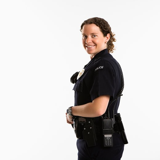 Stock Photo: 1525R-110284 Portrait of mid adult Caucasian policewoman standing with hand on gun holster looking over shoulder at viewer smiling.