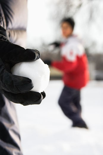 Stock Photo: 1525R-110332 Boy holding snowball ready to throw at boy in background.