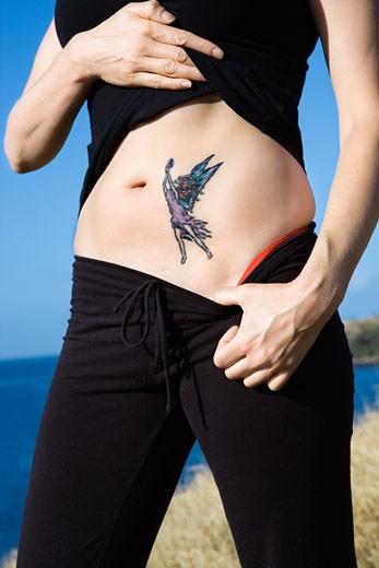 Stock Photo: 1525R-110420 Caucasian woman exposing tattoo of fairy on stomach.