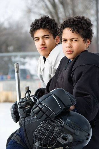 Two boys in ice hockey uniforms sitting on ice rink sidelines looking. : Stock Photo