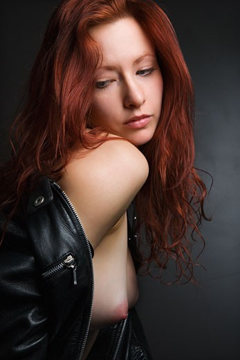 Pretty redhead young woman portrait with leather jacket pulled over shoulder exposing bare breasts. : Stock Photo