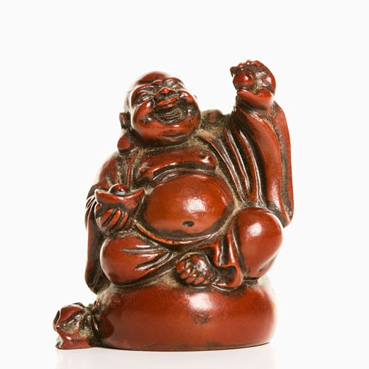 Happy laughing Buddha figurine with hand raised in blessing on white background. : Stock Photo
