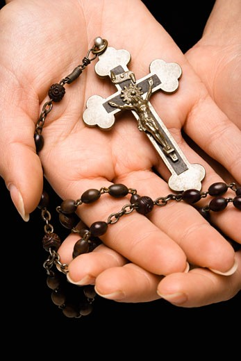 Woman's hands palm up cradling rosary with crucifix. : Stock Photo