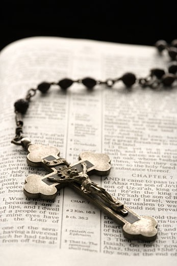 Rosary with crucifix lying on open Bible. : Stock Photo