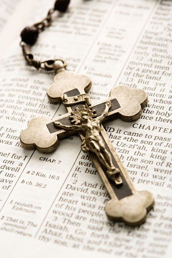 Crucifix on rosary lying on open Bible. : Stock Photo