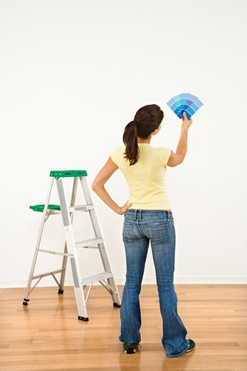 Stock Photo: 1525R-111367 Woman standing in front of white interior wall with paint sample cards trying to choose color.