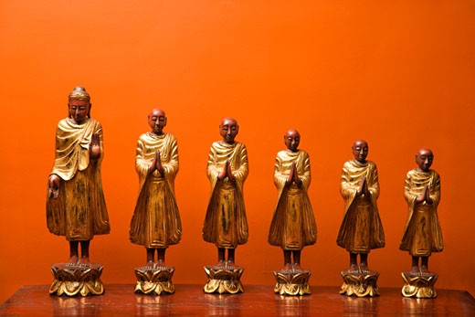 Stock Photo: 1525R-111432 Wooden statues of Buddha with five disciples against orange wall.