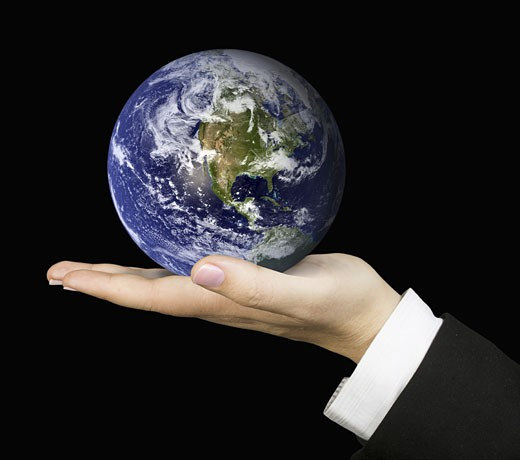 business hand holding globe over a black background : Stock Photo