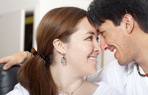 couple at home facing each other while smiling - lifestyle portrait : Stock Photo