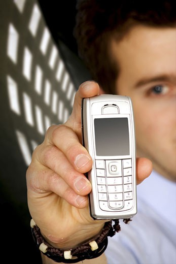 business man holding a mobile phone over a dark background : Stock Photo