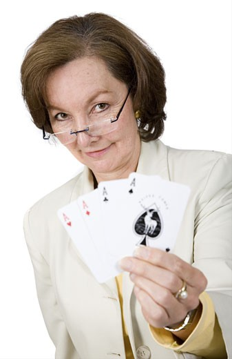 business success - woman holding a winning hand with her cards over white : Stock Photo