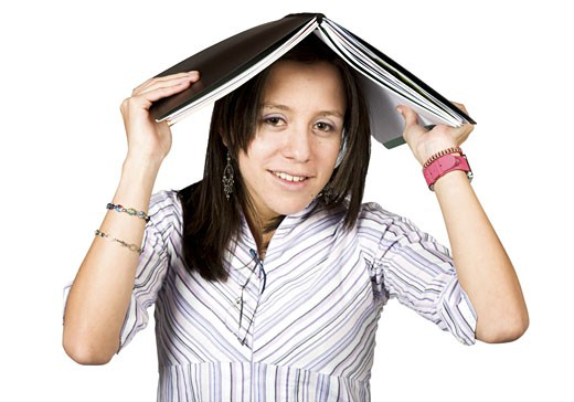 female student with book on head over white : Stock Photo