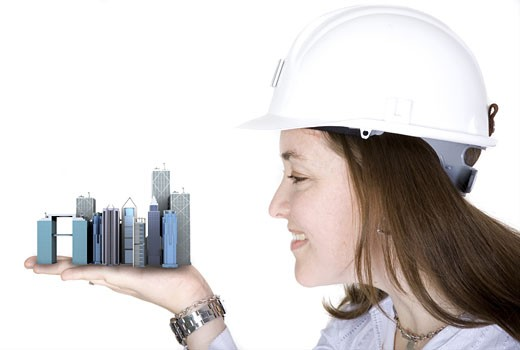 architecture project - woman holding buildings over a white background : Stock Photo