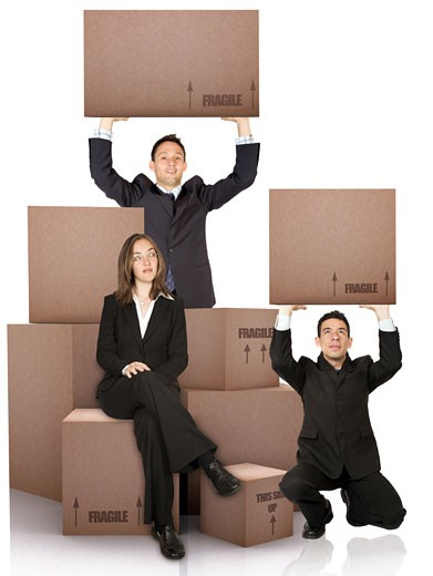 business woman with packed cardboard boxes and two men over a white background : Stock Photo