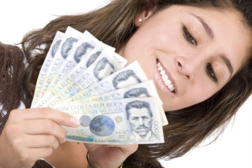 beautiful girl with lots of money - colombian pesos is the currency she is holding : Stock Photo