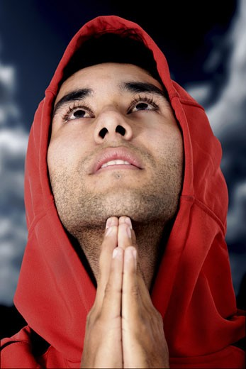 Stock Photo: 1525R-115641 casual guy praying outdoors in a park over a dark sky