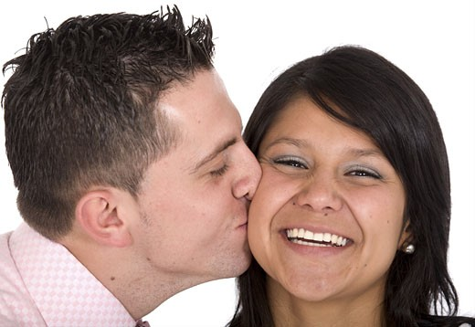 Stock Photo: 1525R-115647 guy kissing his girlfriend on a cheek over a white background