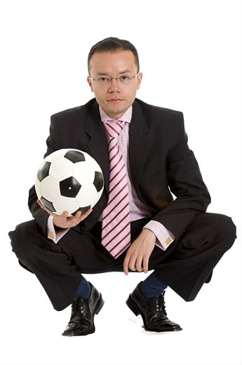 Stock Photo: 1525R-115960 business man and a football over a white background