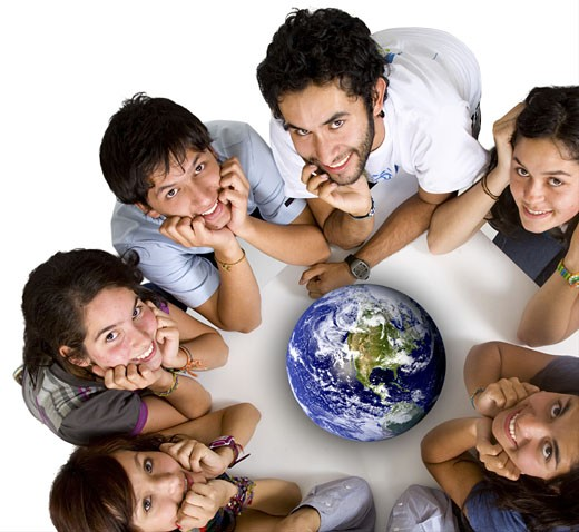 group of young ecologists smiling at the camera with a globe in the middle of them : Stock Photo