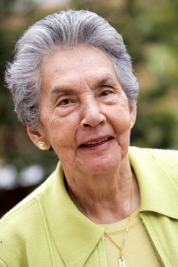 happy retired woman portrait smiling outdoors in green colours : Stock Photo