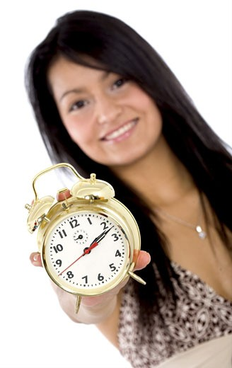 Stock Photo: 1525R-116226 alarm clock held by a beautiful girl isolated over a white background