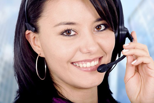 customer service girl smiling with hand on headset - in an office environment : Stock Photo