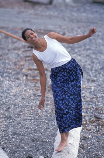 Stock Photo: 1525R-11728 Smiling African American Woman Standing On A Log On A Rocky Beach