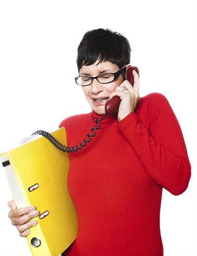 Stock Photo: 1525R-117662 Beautiful young woman with charming big green eyes is bearing modern glasses and receiving calls on a landline phone.