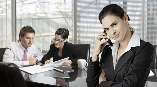 Businesspeople work in the office while a businesswomen talks on mobile in the foreground. : Stock Photo