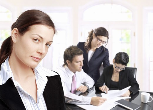 Businesswoman and her team work in a brightly lit office. : Stock Photo