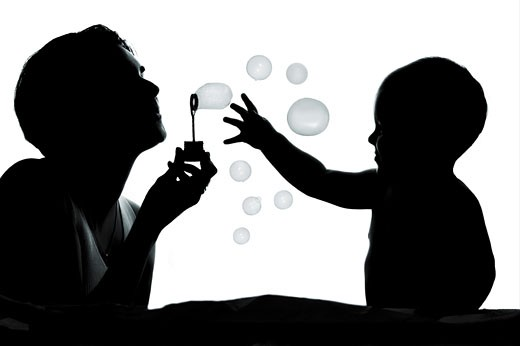1 year old baby and his mother are playing together with bubbles. They are silhouetted. : Stock Photo