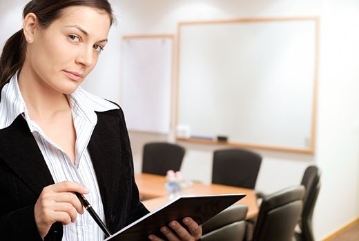Stock Photo: 1525R-117990 Young businesswoman standing in meeting room with blank whiteboards in the background.