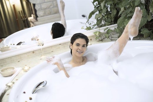 Young woman enjoys the bath in a whirlpool tube. : Stock Photo