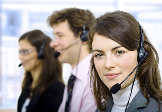 Stock Photo: 1525R-118254 Customer service team working in headsets, smiling.