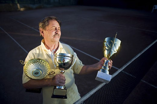 Active senior man in his 70s is posing on the tennis court with cups in hands. Outdoor, sunlight. : Stock Photo