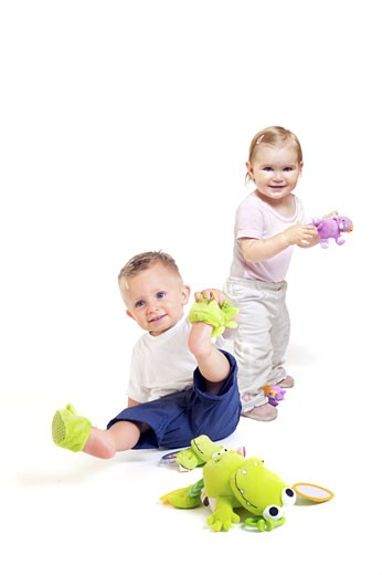 One year old babies (a boy and a girl) enjoy playing with toys. Studio Shot. All toys visible on the photo are officialy property released. : Stock Photo