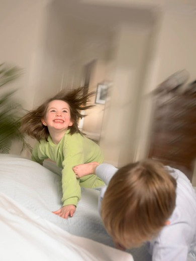 Brother And Sister Wrestling In The Morning : Stock Photo