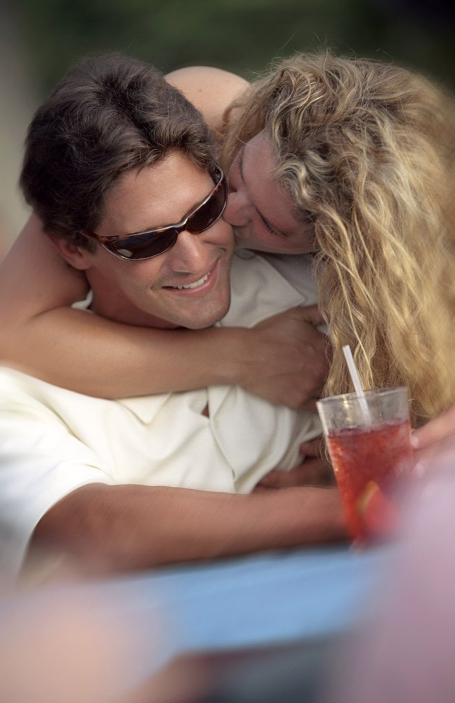 Woman Kissing Man At Sidewalk Cafe : Stock Photo