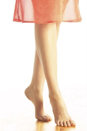 Woman tiptoeing across floor in bare feet 2 : Stock Photo