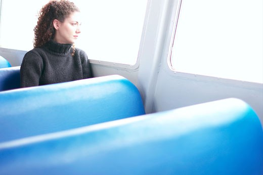 Young woman sitting on a bus looking out the window : Stock Photo